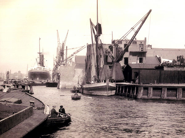 Ship docked at riverside wharf in 1930s